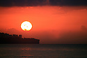 A sunrise against a red sky over the Mediterranean in Antalya, Turkey in November.