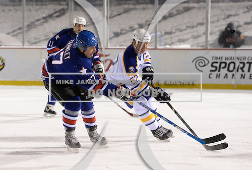 Dan Frawley (27) shoots the puck on goal in front of Craig Rivet (52) during The Frozen Frontier Buffalo Sabres vs. Rochester Amerks Alumni Game at Frontier Field on December 15, 2013 in Rochester, New York.  (Copyright Mike Janes Photography)