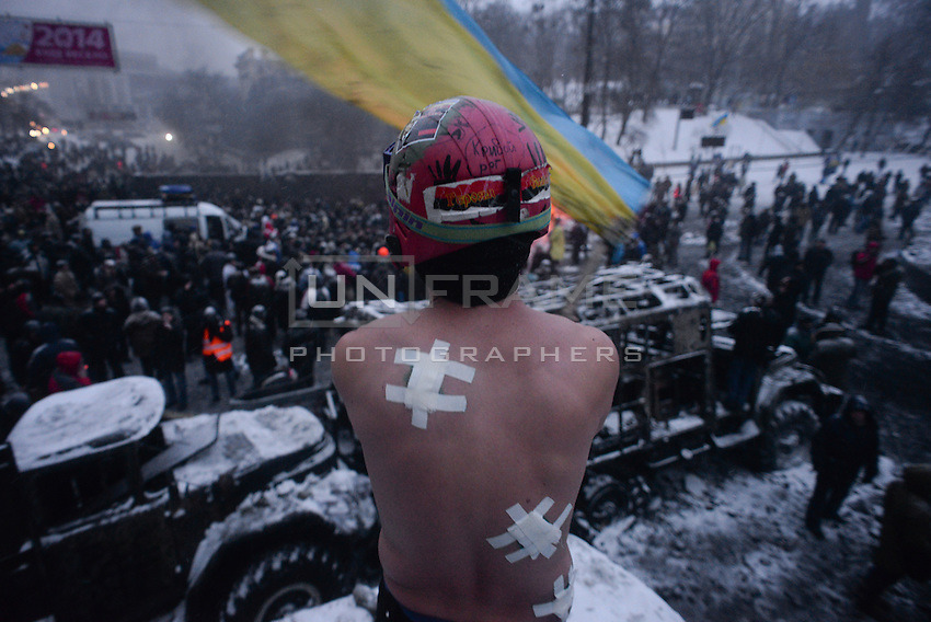 A shirtless protester waves an Ukrainian flag on top of a barricade under the snow during the protest against new draconian law to ban protests across the country.  Kiev. Ukraine