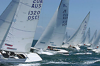 Etchells line up at the start of a sailing race.