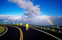 An organized downhill bike tour cruising through the Haleakala Ranch at 5,000 ft. elevation with a rainbow off the North Shore of Maui.