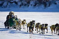Jeff King hunkers behind his sled on the Unalakleet river as he nears Unalakleet on Sunday afternoon