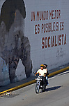 """A motorcycle passes by a wall painting with the face of Venezuelan President Hugo Chavez  with a phrase reading """"a better world is possible, if it's socialist"""" in Caracas, Venezuela, on Saturday, Jul. 08, 2006. (ALTERPHOTOS/Alvaro Hernandez)"""