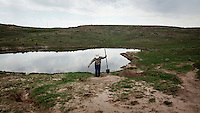 Kevin Larrabee digs a channel by a pond on his ranch in Mead, Kansas. The farm has belonged to his family for over a hundred years. Kevin breeds and raises cattle here in sustainable manner that allows animals to roam freely on the pasture and feed on the grass. ..
