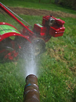 Red Troy-bilt tiller sitting on grass next to recently tilled garden is sprayed with water from brass nozzle on rubber hose..