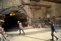 Two workers carry a steel reinforcement beam into the entrance of a tunnel under construction. Construction workers.