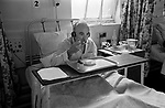 Charing Cross Hospital London 1970S NHS  older man sitting up in bed eating lunch and listening to the radion though ear phones. 1972  England
