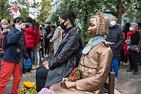 """Protest am Dienstag den 13. Oktober 2020 gegen Entfernung der """"Friedensstatue"""" im Berliner Bezirk Tiergarten-Mitte.<br /> Das Denkmal fuer die sog. """"Trostfrauen"""" steht seit September 2020 und erinnert an die im Zweiten Weltkrieg von den japanischen Besatzern aus Korea verschleppten und zwangsprostituierten Frauen. Es wendet sich als Mahnmal gegen sexualisierte Kriegsgewalt gegen Frauen. Bereits kurz nach der Enthuellung hat die japanische Regierung gegen dieses Denkmal protestiert und das Auswaertige Amt, sowie den Berliner Senat und den Bezirk aufgefordert die bronzene Statue, eine sitzende Frau und ein leerer Stuhl, entfernen zu lassen. Der Bezirksbuergermeister von Berlin Tiergarten-Mitte, Stephan von Dassel (Buendnis 90/Die Gruenen) hat die Entfernung des Mahnmals angeordnet. Dagegen protestierten am 13. Oktober 2020 mehrere hundert Menschen und zogen mit einer Demonstration vor das Rathaus des Bezirkbsuergermeister.<br /> 13.10.2020, Berlin<br /> Copyright: Christian-Ditsch.de"""