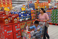 A mother pushes her child in a trolley through a supermarket in Chengdu, China. A rapidly expanding middle class has created a large market for many products not previously sold in China..20 Sep 2006