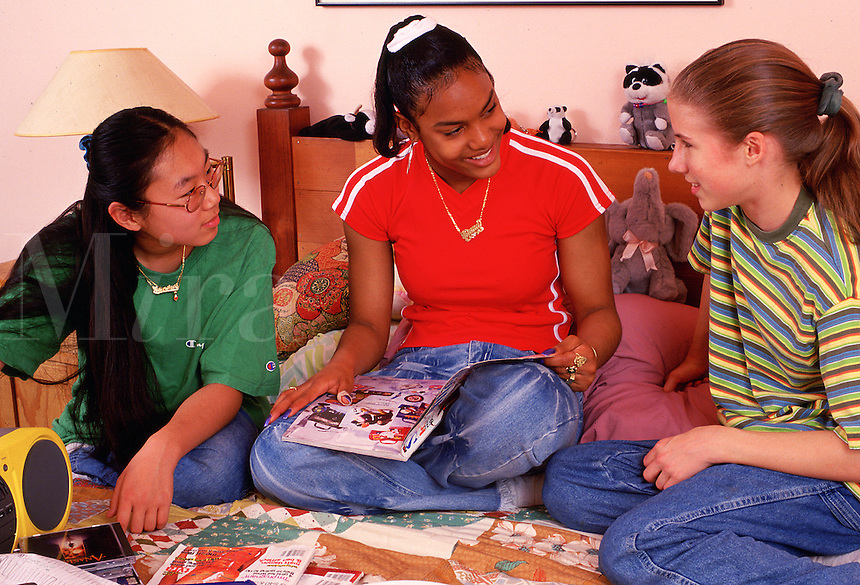 Three friends - Korean, African-American, and Caucasian - speak together in the bedroom