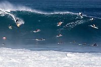 A surfer navigates through a crowded lineup on a big wave at Pipeline (off of 'Ehukai Beach Park), North Shore, O'ahu.