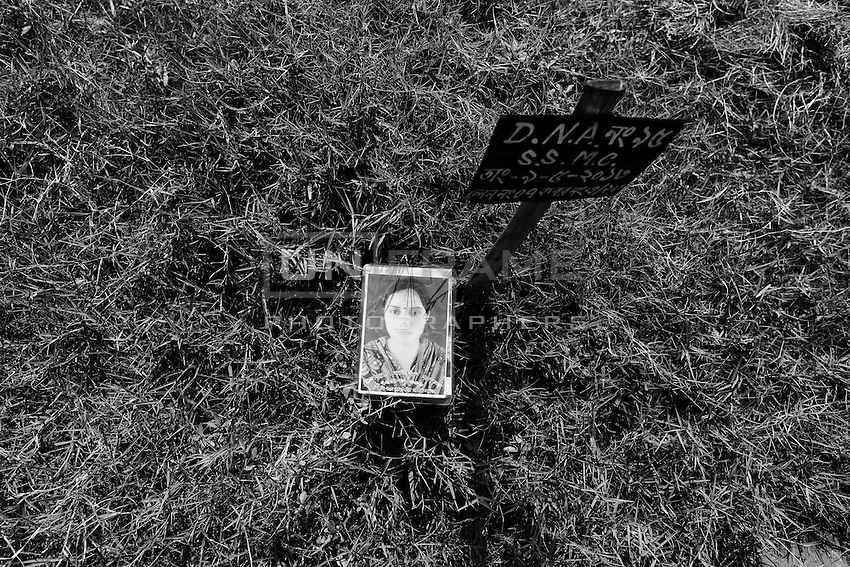 """Morjina Khatun's father  puts an image of his daughter on the grave number """"DNA Number 95, S.S.M.C, Lane 7, Grave A/23"""" in Jurain graveyard, Dhaka, Bangladesh"""