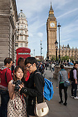 Tourists with camera by red phone box and Big Ben London Parliament Square