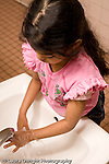 Education Preschool 4-5 year olds ealth and hygiene girl washing her hands in bathroom sink vertical
