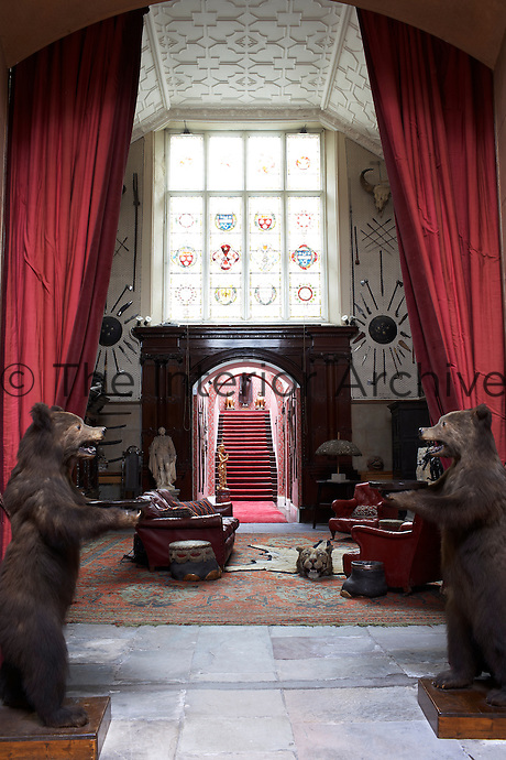 Inside the house on the Clandeboye estate, which is the home to Lady Dufferin, Marchioness of Dufferin and Ava. The dramatic entrance to the inner hall with deep red curtains and a pair of stuffed bears, acquired by the 1st Marquess, guarding the way to the baronial-proportioned space. The stained glass window represents the arms of the families linked with Clandeboye.