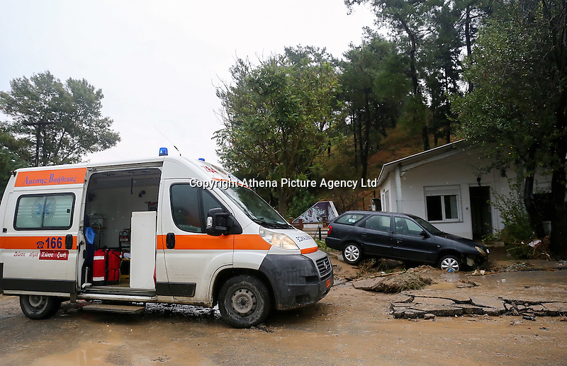 An ambulance next to a car that is resting on a pile of mud and debris in Agia Triada