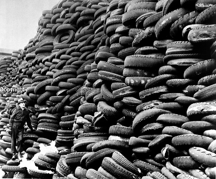As this big pile of used auto tires indicates, the United States with its many passenger cars has in discarded tires a large source of reclaimed rubber for use in the war effort.  (OWI)<br /> Exact Date Shot Unknown<br /> NARA FILE #:  208-AMC-3D-1<br /> WAR & CONFLICT #:  789