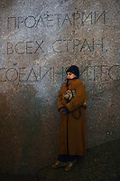 "Moscow, Russia, 28/10/2011..A woman watching the gala reopening of the Bolshoi Theatre on a giant video screen while standing on the plinth of a statue of Karl Marx with the inscription ""Workers of the world unite"". The theatre had been closed since 2005 for reconstruction work that cost some $700 million."