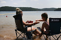 Ashley Laughlin of Seneca, Mo. (from left) and Kynley Laughlin, 11, enjoy a snack, Saturday, July 31, 2021 at the lake at Horseshoe Bend Campground in Rogers. Check out nwaonline.com/210801Daily/ for today's photo gallery. <br /> (NWA Democrat-Gazette/Charlie Kaijo)