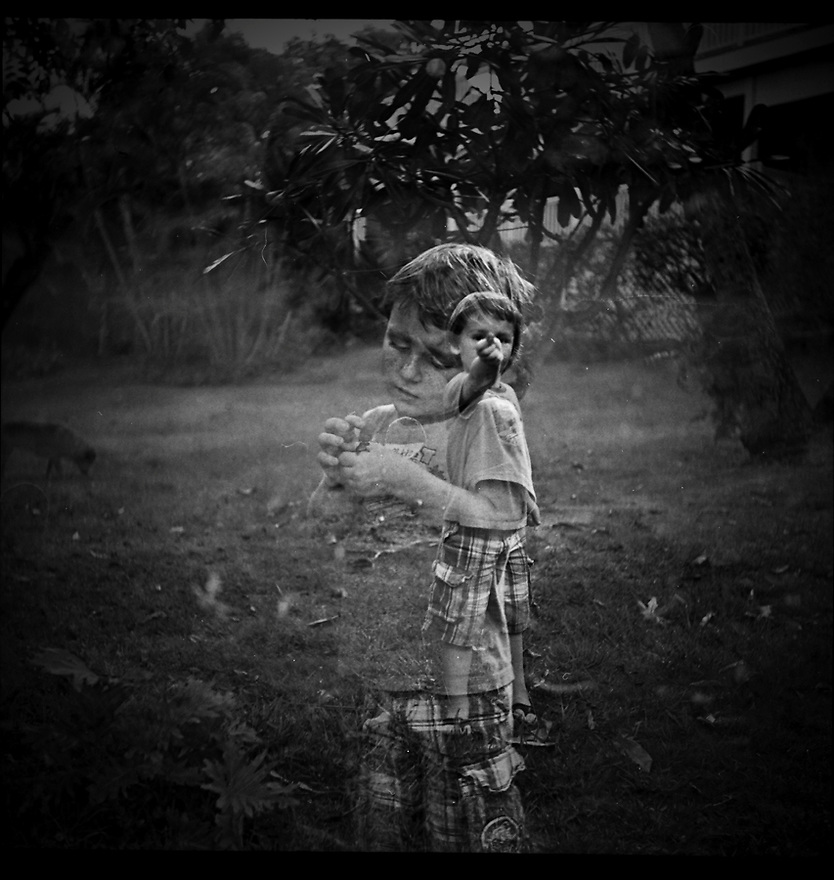 Lizard King.  Small boy holding lizard.  Double exposure using Yashica A Twin Lens Reflex and Fuji Neopan 400 film by Liisa Roberts.