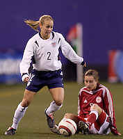 """USA's Heather Mitts gets past a fallen Johanna Rasmussen of Denmark. The US Women's National Team tied the Denmark Women's National Team 1 to 1 during game 8 of the 10 game the """"Fan Celebration Tour"""" at Giant's Stadium, East Rutherford, NJ, on Wednesday, November 3, 2004.."""