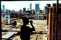 A child looks over the Boston Harbor and skyline from his hotel-room window.