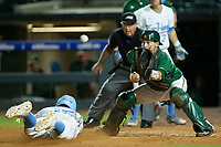 Miami Hurricanes catcher Joe Gomez (40) waits for the throw as Michael Busch (15) of the North Carolina Tar Heels slides head first across home plate in the second semifinal of the 2017 ACC Baseball Championship at Louisville Slugger Field on May 27, 2017 in Louisville, Kentucky.  The Tar Heels defeated the Hurricanes 12-4.  (Brian Westerholt/Four Seam Images)