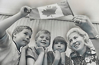 Going to Moscow for the Canada-Soviet Union hockey series; Deborah Lappin; an Agincourt widow; will take a Canadian flag with her. She says she's become a real hockey nut since her sons (from left) Bradley; 4; Brian; 7; and Bruce; 9; began playing. A total of 2;700 Canadians are booked on 11 charter flights to Moscow. Tickets to Canadian games are being sold to persons winning a lottery draw.