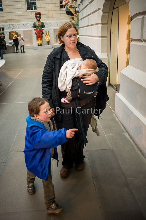 A mother breastfeeding her baby from a sling in a museum.<br /> <br /> London, England, UK<br /> 08/03/2015<br /> <br /> © Paul Carter / wdiip.co.uk