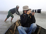 Deddeda takes photos in a boat on the Rapti River in Chitwan national Park, Nepal.