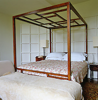 A contemporary Chinese-style four-poster bed against a white-painted panelled screen in a guest bedroom at Bowling Green
