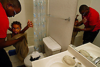 Sgt. Rickey Moore helps his son Rickey Jr., 5, dry off after his bath Monday night, March 17, 2003. Rickey spent most of his last night, before his deployment, home with his family following in their  natural routines. They ate dinner together and spent quiet time with each other at home. The only clue something might be different, were the voices of news anchors from one of the 24 hour news stations speaking about the new 48 hour countown to war laid out in the Presidential address earlier that evening.(Kelly Jordan)..**FOR ONLINE DEPLOYMENT GALLERY**