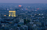 Arc de Triomphe illuminated at twilight surrounded by the cityscape of Paris, France.