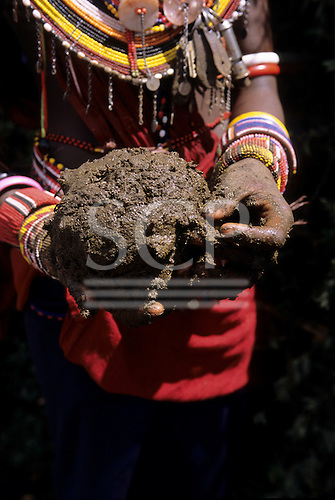 Lolgorian, Kenya. Female Siria Maasai with colourful bead necklaces helping to build the manyatta using cow dung; Eunoto ceremony