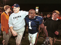 A rare smile emits from UVa head Coach Al Groh, left, as he walks with running back Antwione Womack and fans after a stunning victory over Penn State.