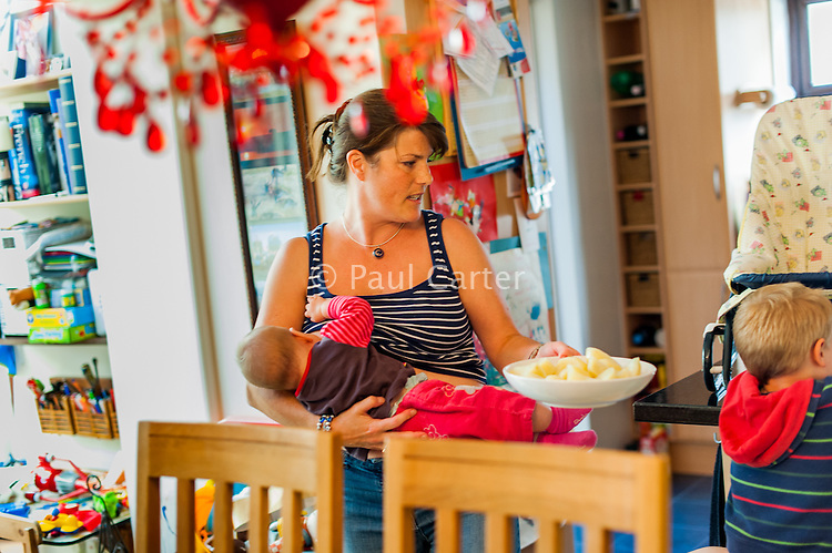 A mother breastfeeds her baby while preparing for lunch in the dining room.<br /> <br /> 30 August 2012<br /> Hampshire, England, UK