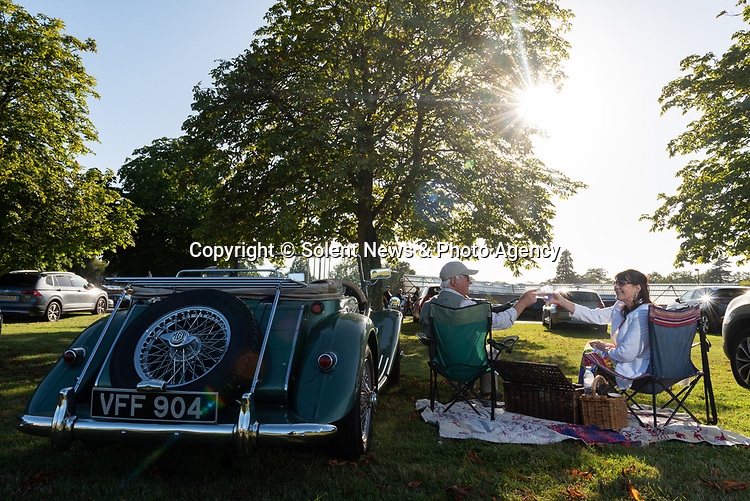 Pictured: Chris Richards and Ann Marie Webley toast a drink next to their 1954 MG TF 1500 during the Park & Picnic event at National Motor Museum, Beaulieu in the New Forest, Hants.<br /> <br /> The Park and Picnic event, allows motorists to park in bays designated for social distancing regulations and enjoy an evening of music and entertainment on the grounds of the National Motor Museum, Beaulieu.<br /> <br /> © Jordan Pettitt/Solent News & Photo Agency<br /> UK +44 (0) 2380 458800