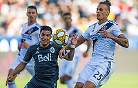 CARSON, CA - SEPTEMBER 29: Michaell Chirinos #33 of the Vancouver Whitecaps and Rolf Feltscher #25 of the Los Angeles Galaxy battle for a ball during a game between Vancouver Whitecaps and Los Angeles Galaxy at Dignity Health Sports Park on September 29, 2019 in Carson, California.