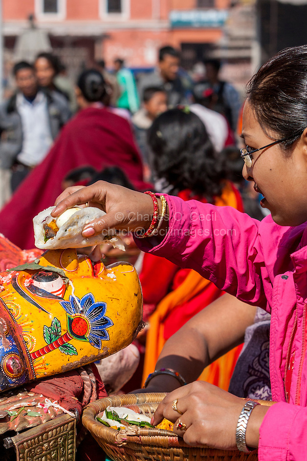 Bhaktapur, Nepal.  Woman Presenting Offering of Food to a mask Representing a Hindu Deity.