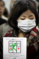 A commuter, wearing a surgical mask, crammed into one of the train carriages at Shibuya station during morning rush hour.