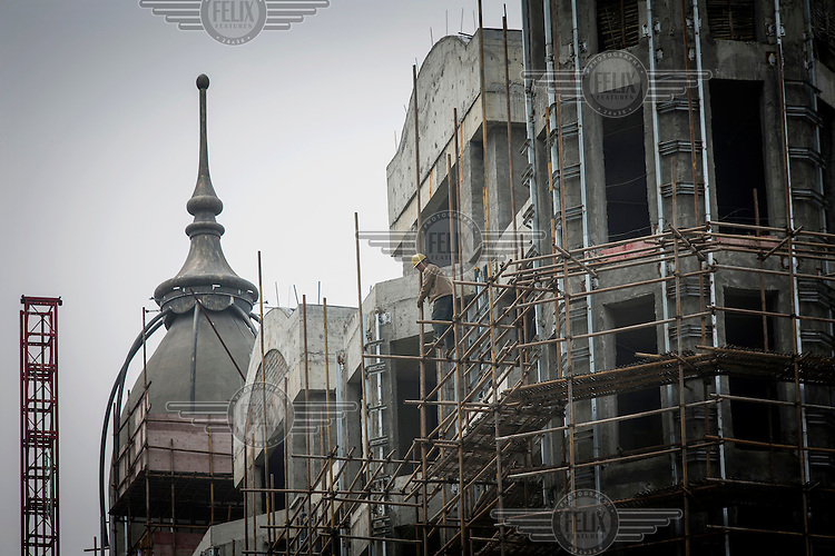 A worker stands on a scaffolding at the construction site of the Yulong Palace real estate development.