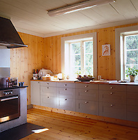 Grey Shaker-style cabinets furnish this modern pine-clad kitchen