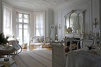 The large panelled living/dining room is furnished with a Gustavian sleigh, sofa, wooden settle and dining table