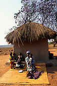 Kapatu, Zambia. Woman with her five children outside their thatched adobe house sitting on reed mats.
