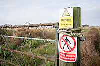 Farm gate with signs and barbed wire