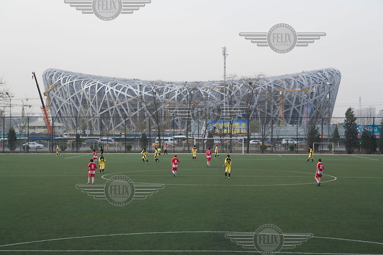 A school football match takes place across the highway from the construction of the Beijing National Stadium, also known as the Bird's Nest, being built for the 2008 Olympic Games.