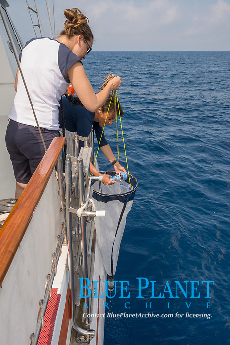 Viridiana Jimenez-Moratalla Pelhate, principal investigator for CSR research cruise of Tethys Research Institute holds a plankton sampling net while program director Sabina Airoldi checks the data recorder; Pelagos Sanctuary, Ligurian Sea, Italy (Mediterranean Sea)