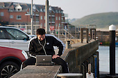 A man sitting on the harbour wall in Padstow, Cornwall, using a laptop.