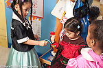 Education Preschool 3-4 year olds group of girls talking in pretend play area talking about game wearing dressup clothes