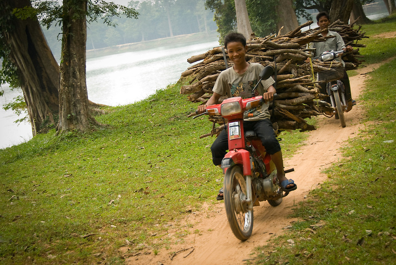 Boys are transporting wood on the interior road at Angkor Wat, Cambodia. With increased wealth in Cambodia motorbikes are slowly gaining in popularity especially in cities. As you can see they are used to transport good of all kinds and it is not uncommon to see a family of five on a motorbike!